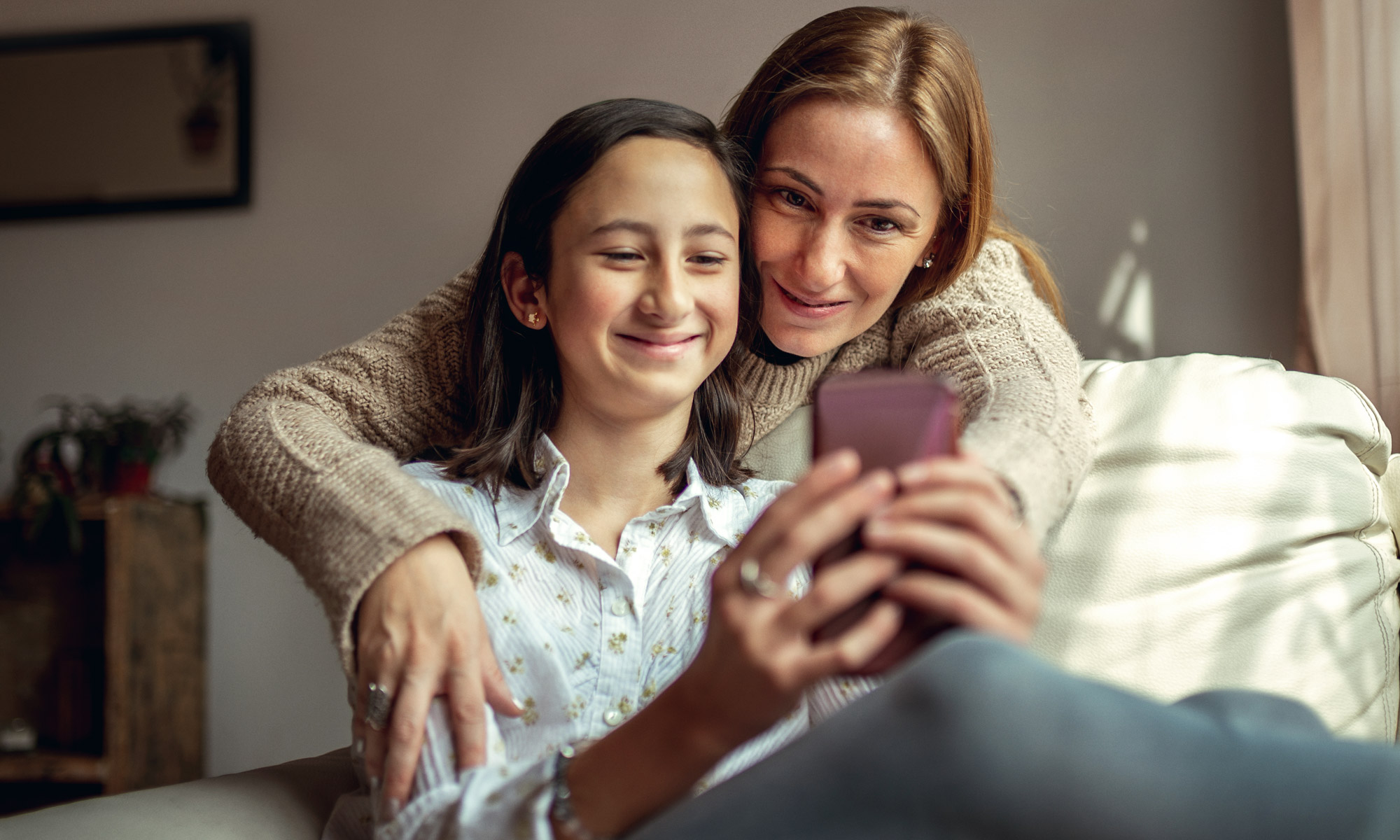 Woman and daughter looking at phone